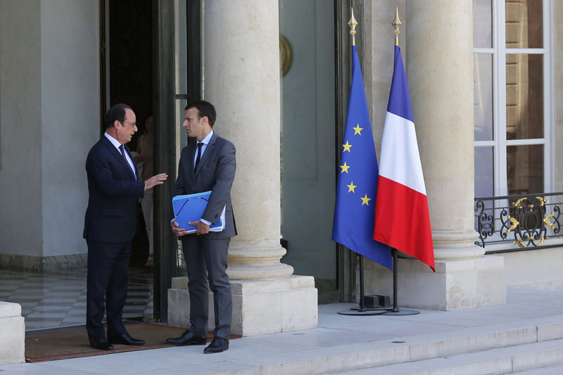 File picture shows French President Francois Hollande (L) as he escorts French Economy Minister Emmanuel Macron while leaving the Elysee Palace following the weekly cabinet meeting, in Paris, France, July 31, 2015. REUTERS/Stephane Mahe/FileCODE: X02520