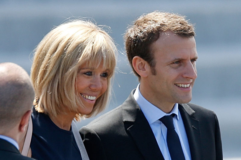 French Economy Minister Emmanuel Macron (R) and his wife Brigitte Trogneux attend the Bastille Day military parade on the Champs-Elysees in Paris, France, July 14, 2016. REUTERS/Charles PlatiauCODE: X00217