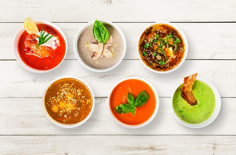 Variety of restaurant hot dishes, healthy food. Japanese miso soup, asian fish soup, russian borscht, english pea soup with bacon, mushroom soup, spanish gazpacho at white rustic wood, top view