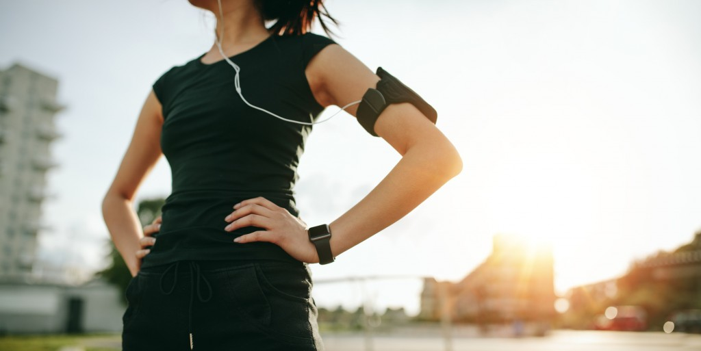Cropped shot of urban runner outdoors in sunny morning. Fit young woman with smartwatch and mobile phone armband standing with her hands on hips.