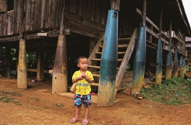 "A boy stands in front of a house built on bombs dropped by the U.S. Air Force planes during the Vietnam War, in the village of Ban Napia in Xieng Khouang province, Laos September 3, 2016. REUTERS/Jorge Silva         SEARCH ""LAOS BOMBS"" FOR THIS STORY. SEARCH ""WIDER IMAGE"" FOR ALL STORIES. - RTX2O6OQ"