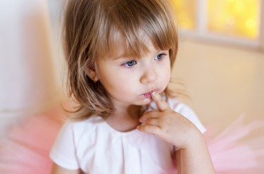 Girl holding finger in mouth