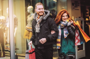 Young couple walking in front of  store windows. Holding shopping bags. Wearing warm clothes, hats and scarves. Vienna, Austria. Smiling and talking.
