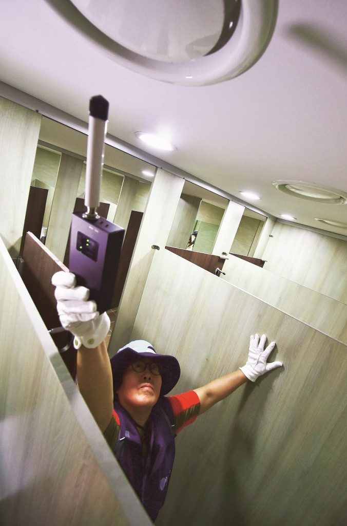 "This picture taken on August 18, 2016 shows a member of Seoul city's ""hidden camera-hunting"" squad waving a hand-held detector around the ventilation grill on the ceiling of a women's bathroom stall to find ""secret camera"" at a museum in Seoul. South Korea takes pride in its tech prowess, from ultra-fast broadband to Samsung's cutting-edge smartphones. But it's a culture that has also given rise to an army of tech-savvy peeping Toms in a still male-dominated country with a poor record on women's rights. / AFP / JUNG YEON-JE / TO GO WITH AFP STORY: SKorea-technology-crime-gender, FEATURE by Jung Hawon (Photo credit should read JUNG YEON-JE/AFP/Getty Images)"
