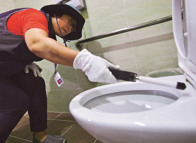 "This picture taken on August 18, 2016 shows a member of Seoul city's ""hidden camera-hunting"" squad waving a hand-held detector around the toilet seat of a women's bathroom stall to find ""secret camera"" at a museum in Seoul. South Korea takes pride in its tech prowess, from ultra-fast broadband to Samsung's cutting-edge smartphones. But it's a culture that has also given rise to an army of tech-savvy peeping Toms in a still male-dominated country with a poor record on women's rights. / AFP / JUNG YEON-JE / TO GO WITH AFP STORY: SKorea-technology-crime-gender, FEATURE by Jung Hawon (Photo credit should read JUNG YEON-JE/AFP/Getty Images)"