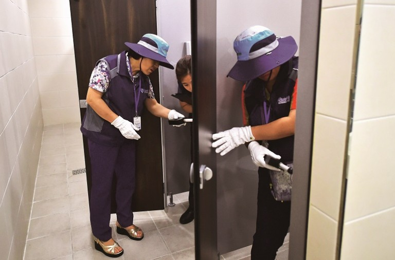 "This picture taken on August 18, 2016 shows members of Seoul city's ""hidden camera-hunting"" squad inspecting a women's bathroom stall to find ""secret camera"" at a museum in Seoul. South Korea takes pride in its tech prowess, from ultra-fast broadband to Samsung's cutting-edge smartphones. But it's a culture that has also given rise to an army of tech-savvy peeping Toms in a still male-dominated country with a poor record on women's rights. / AFP / JUNG YEON-JE / TO GO WITH AFP STORY:  SKorea-technology-crime-gender, FEATURE by Jung Hawon        (Photo credit should read JUNG YEON-JE/AFP/Getty Images)"