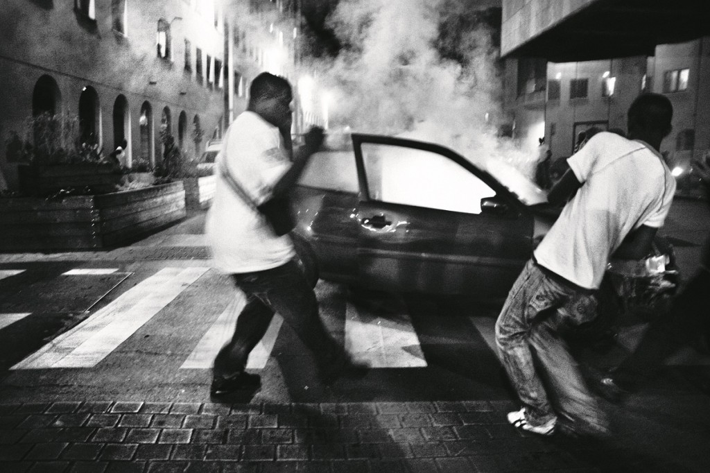 A group of men throw powerful firecrackers into an stolen car in order to burn it in the streets of Saint Denis on the National Day of France. As a sign of protest these firecrackers are used to throw against the police during the National Day of France and also in the revolts of the suburbs. Saint Denis, Paris, Île-de-France province, France on July 13, 2007. Oct. 27, 2005, in Clichy-sous-Bois, a northern suburb of Paris, Zyed Benna and Bouna Traoré, 15 and 17 years old respectively, died electrocuted, while they hid from police in an electrical transformer. In the next hours, friends and neighbors took to the streets in protest. This provoked clashes with security forces that quickly spread throughout Parisian suburbs. In the following days, the revolt burned through numerous periphery areas throughout the country, until Nov. 8, 2005 when the French government declared a state of an emergency.