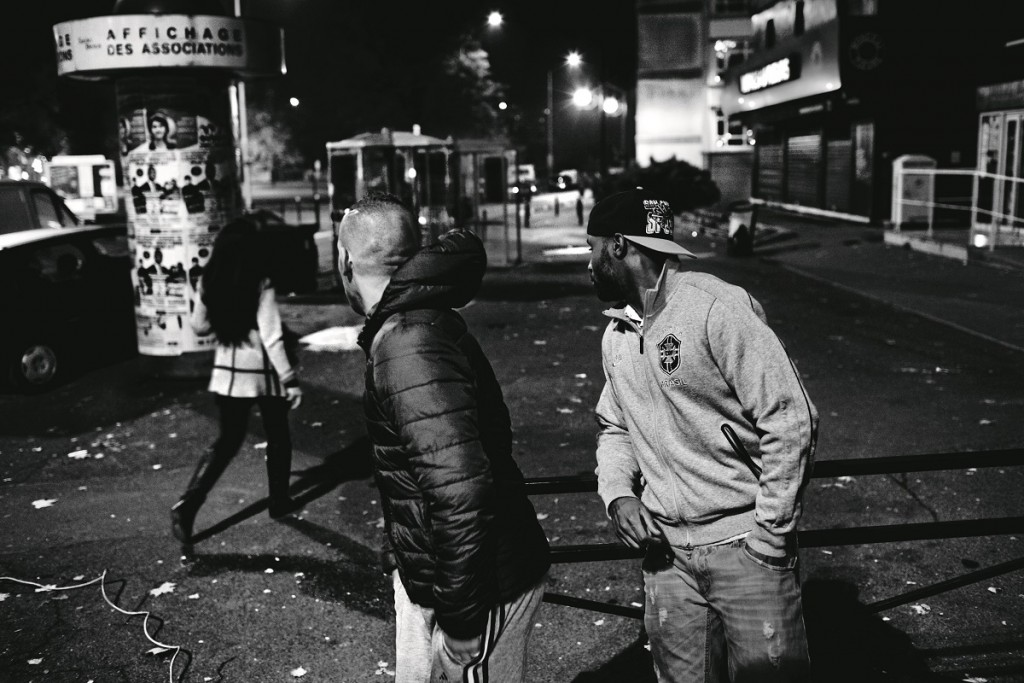 Two guys flatters a women who walks through the streets of Saint Denis. Saint Denis, Paris, Île-de-France province, France on November 13, 2012. Oct. 27, 2005, in Clichy-sous-Bois, a northern suburb of Paris, Zyed Benna and Bouna Traoré, 15 and 17 years old respectively, died electrocuted, while they hid from police in an electrical transformer. In the next hours, friends and neighbors took to the streets in protest. This provoked clashes with security forces that quickly spread throughout Parisian suburbs. In the following days, the revolt burned through numerous periphery areas throughout the country, until Nov. 8, 2005 when the French government declared a state of an emergency.
