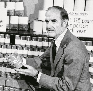 "Sen.George McGovern, D-S.D., displays cans of sodas, sugar and fat which he say represent a persons average intake for a year, during a press conference in Washington Friday. January 14, 1977. McGovern, chairman of the Senate Nutrition Committee, held the conference to release a panel report.""Dietry goals for the United States ."" (AP Photo)"