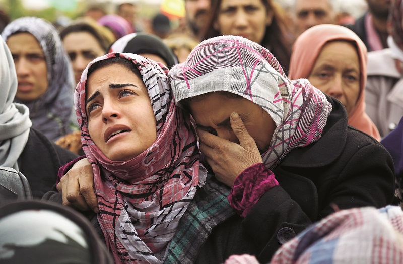 TOPSHOT - The sister (L) of Mohammed Ismael, who died in one of three suicide car bombings claimed by the Islamic State (IS) group in the nearby town of Tal Tamr earlier this week, mourns during his funeral in Qamishli, a Kurdish-majority city in Syria's northeastern Hasakeh province, on December 13, 2015. Tal Tamr, in the Khabur region, is controlled by Kurdish forces and has been targeted in the past by IS jihadists, who in February overran much of Khabur and kidnapped at least 220 Assyrian Christians. AFP PHOTO / DELIL SOULEIMAN / AFP / DELIL SOULEIMAN (Photo credit should read DELIL SOULEIMAN/AFP/Getty Images)