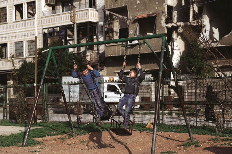 Syrian children play on a swing at a park in the rebel-held town of Douma, on the eastern edges of the capital Damascus on February 27, 2016, on the first day of the landmark ceasefire agreement. Less than a day into a landmark ceasefire deal in parts of the country, residents say their usual routine has been thrown off without the usual sounds of artillery, rocket attacks, or helicopter-borne barrel bombs. / AFP / Sameer Al-Doumy (Photo credit should read SAMEER AL-DOUMY/AFP/Getty Images)