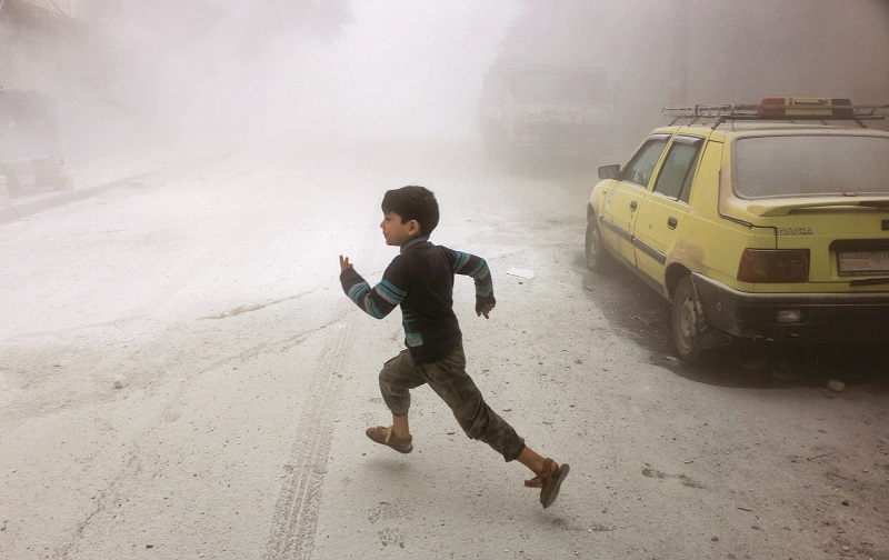 ALEPPO, SYRIA - APRIL 24: A Syrian boy runs after Syrian Regime Forces airstrikes targeted residential areas at Sahur neighborhood in Aleppo, Syria on April 24, 2016. (Photo by Beha el Halebi/Anadolu Agency/Getty Images)