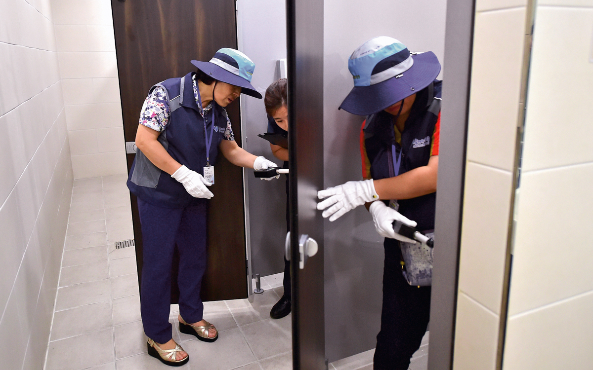 "This picture taken on August 18, 2016 shows members of Seoul city's ""hidden camera-hunting"" squad inspecting a women's bathroom stall to find ""secret camera"" at a museum in Seoul.