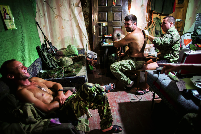 "August 19, 2016 - Mariinka, Ukraine: Ukrainian soldiers on the base. ""Timon"" is getting new tattoo. The Ukraine conflict between Ukrainian government troops and Russian-backed separatists is now in its 30th month, and despite many cease-fires the front line is still very dangerous. About 9,600 people have now been killed and some 22,231 wounded, and around 1.7 million civilians fled their homes rather than remain in the crossfire. Entire towns in the Donbas region of Eastern Ukraine now sit empty and destroyed. The last large push of the war took place in the town of Marinka, on the outskirts of the separatist stronghold of Donetsk, during the summer of 2015. It was thwarted by Ukrainian troops. Since then, the two sides have resorted to battling it out from their heavily entrenched positions using snipers, machine guns, artillery and even tanks. The war drags on for the volunteer soldiers of the UDA. (Dmitri Beliakov/Polaris)"