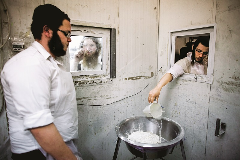 MIDEAST ISRAEL PASSOVER.jpg:epa05265485 Ultra-Orthodox Jews in a sterile room pour water into a bowl from a small window at a Matzah bakery in the southern Israeli city of Ashdod, Israel, 18 April 2016. Matzah, or unleavened bread, is used instead of bread during the week-long Jewish holiday of Passover, commemorating the Jewish exodus from Egypt in Biblical times. EPA/ABIR SULTAN