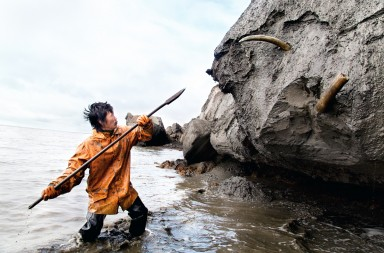 Bolshoy Lyakhovsky Island, Republic of Sakha (Yakutia), Russia, 2012. Slava Dolbaev uses a spear to dig out a tusk from a coastal ice cliff. Mammoth tusk hunters spend up to 6 months on the uninhabited islands in the Laptev Sea in search of the tusks. In spring while the sea is still frozen they arrive by the snowmobiles from the main land coastal villages, when the season is finished they return by the motor boats loaded with their finds.