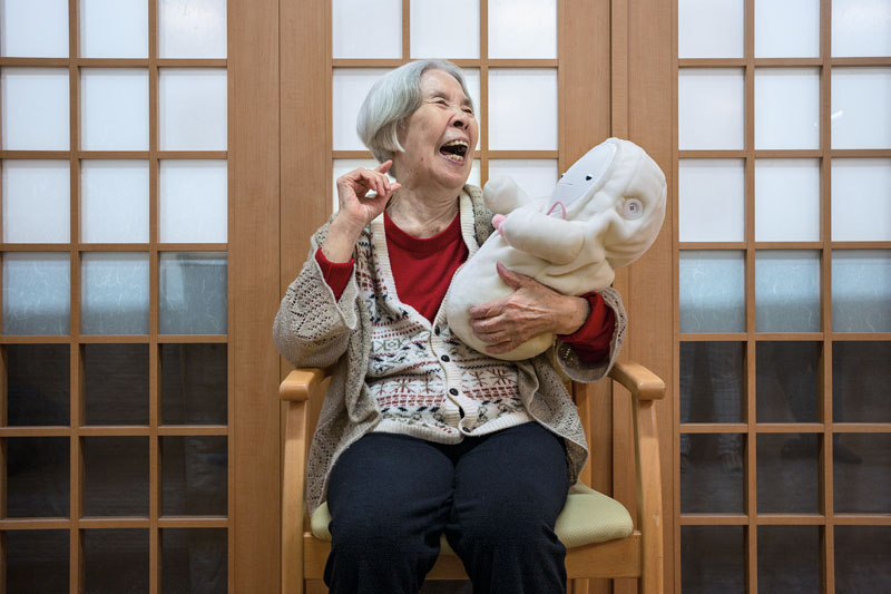 Japon. Seniors. Robot Smiby. Michi. 88 ans Michi, âgée de 88 ans, trouve le robot Smiby plutôt drôle. Smiby a différent types de sourires, il peut pleurer, être triste, fatigué. 500 sentiments sont programmés ainsi que 5 mots gazouillés (maman, grand-mère, serre-moi, j'ai faim, gouzi-gouzi). Sa durée d'utilisation est de 10h ; sa charge de 8h. Japan. Seniors. Smiby robot. Michi. 88 years Michi, 88 years old, finds Smiby robot rather funny. Smiby has different types of smiles, he may cry, be sad, tired. 500 feelings are programmed and 5 warbled words like mom, grandmother, hold me, I'm hungry. Its length of time used is 10 hours; his electric charge is 8 hours.