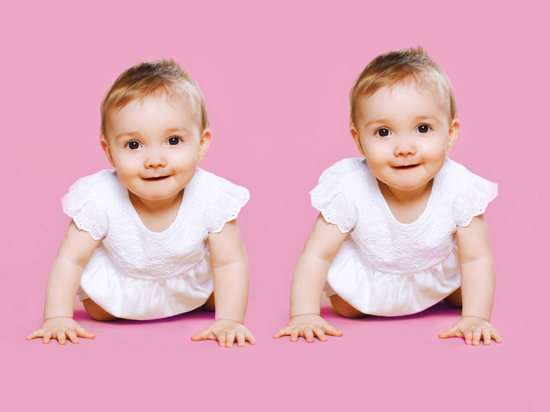 Portrait of two sweet twins baby crawls together