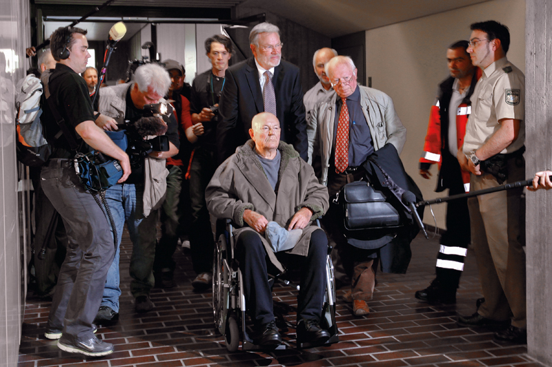 Convicted Nazi death camp guard John Demjanjuk leaves a courtroom after his the verdict in Munich on May 12, 2011. Convicted Nazi camp guard John Demjanjuk, 91, will be released from jail despite his five-year sentence for helping to kill 27,900 Jews at the Nazi death camp Sobibor because of his advanced age, the court said. REUTERS/Michael Dalder (GERMANY - Tags: POLITICS CRIME LAW IMAGES OF THE DAY) - RTR2MB6I