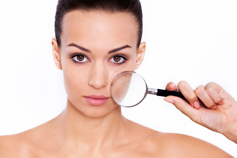 Magnifying facial features. Studio shot of a beautiful woman with a magnifying glass in front of her face