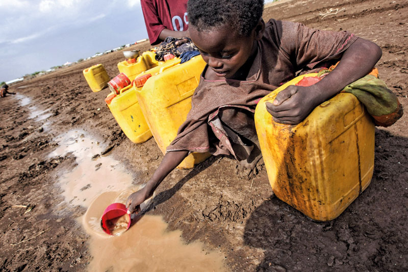 "A child collects water from a puddle after a rainstorm near the Torotoro village, 125 km southwest from Mogadishu, Somalia, on March 27, 2009. According to local news sources at least 12 people have died following an outbreak of acute watery diarrhea (AWD) in villages around the regional capital of Jowhar. A local government official said most water points in the area had dried up or were almost dry, ""They are desperate and unfortunately, resorting to desperate measures"". AFP PHOTO / MOHAMED DAHIR (Photo credit should read MOHAMED DAHIR/AFP/Getty Images)"