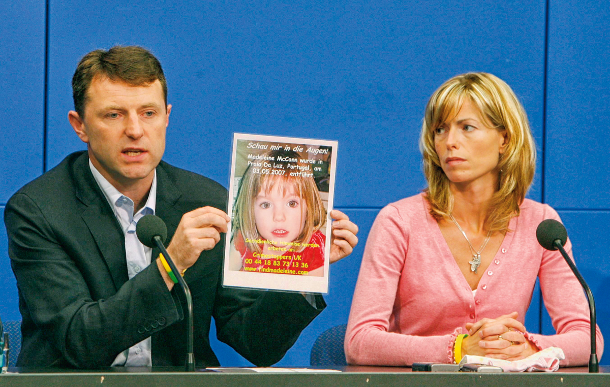 Kate and Gerry McCann, parents of missing British girl Madeleine McCann, hold a poster during a news conference in Berlin June 6, 2007. Gerry and his wife Kate are visiting Germany to meet politicians later on Wednesday. The poster reads 'Look into my eyes - Madeleine McCann was abducted in Praia da Luz, Portugal on May 3, 2007'.       REUTERS/Alex Grimm (GERMANY)