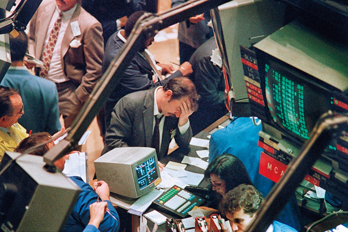 A trader (c) on the New York Stock Exchange reacts on October 19, 1987 as stocks are devastated during one of the most frantic days in the exchange's history. The Dow Jones index plummeted over 200 points in record trading. / AFP PHOTO / MARIA BASTONE        (Photo credit should read MARIA BASTONE/AFP/Getty Images)