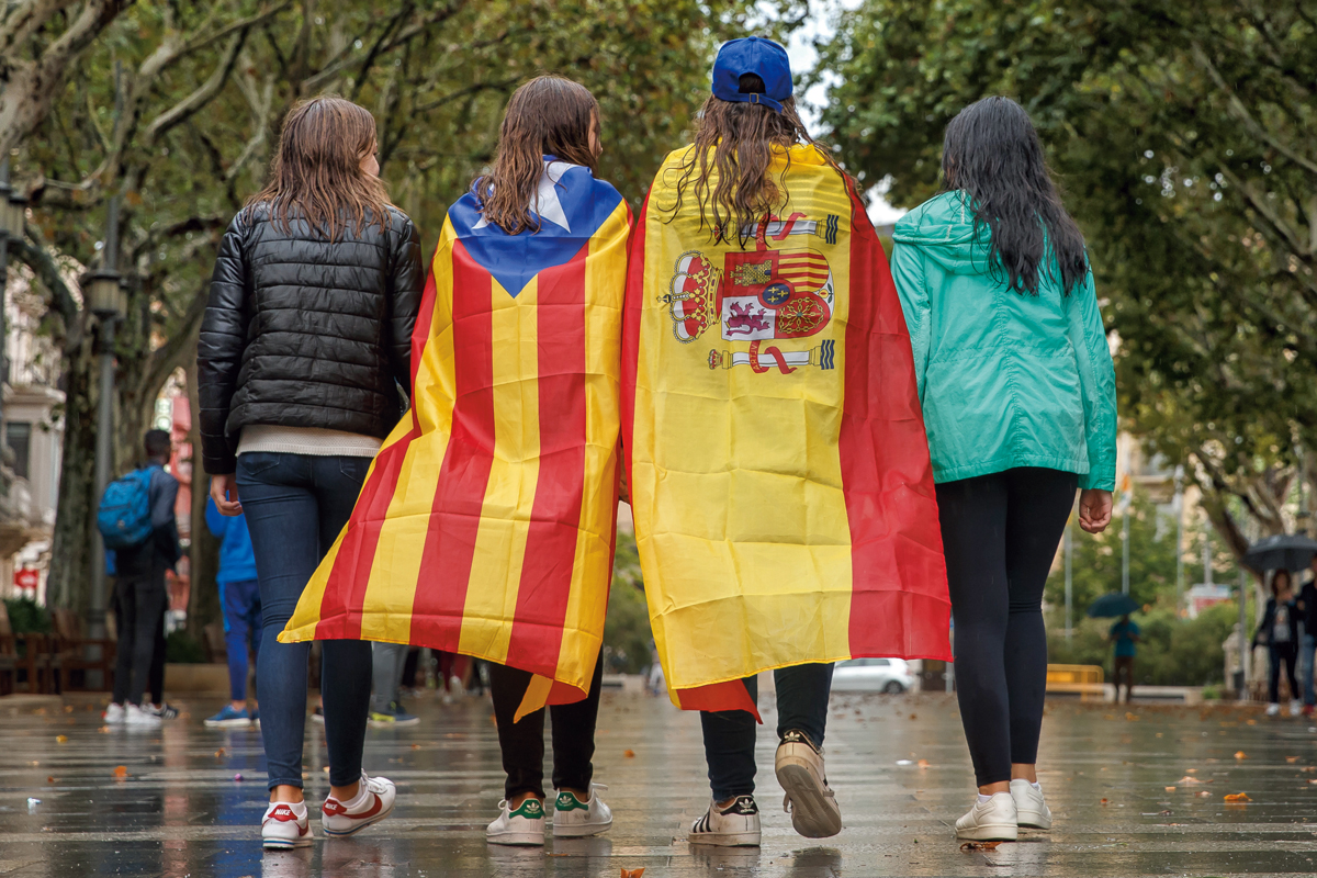 Girls stroll through the center of Figueras with the Spanish and a pro-independence 'Estelada' Catalan flag on September 30, 2017 in Figueras.  Catalan separatists showed determination today to press ahead with an independence referendum banned by Madrid, occupying dozens of schools designated as polling stations to stop police from closing them down. / AFP PHOTO / CESAR MANSO        (Photo credit should read CESAR MANSO/AFP/Getty Images)
