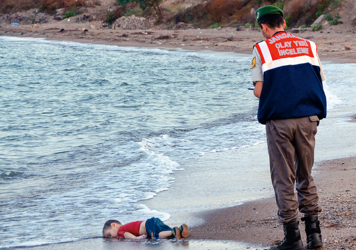 FOR USE AS DESIRED, YEAR END PHOTOS - FILE - A paramilitary police officer investigates the scene before carrying the lifeless body of 3-year-old Aylan Kurdi from the sea shore, near the beach resort of Bodrum, Turkey, early Wednesday, Sept. 2, 2015. A number of migrants are known to have died and some are still reported missing, after boats carrying them to the Greek island of Kos capsized. (AP Photo/DHA, File) TURKEY OUT