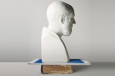 White plaster bust of Hyppocrates with pencil behind his ear and black rimmed glasses