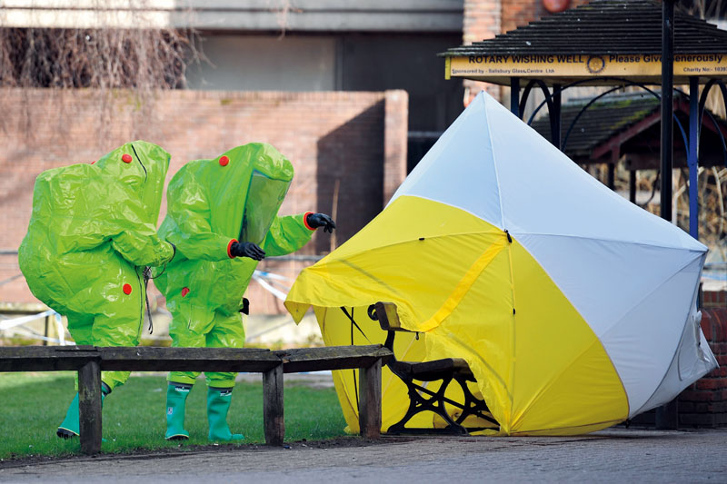 """Members of the emergency services in green biohazard encapsulated suits afix the tent over the bench where a man and a woman were found on March 4 in critical condition at The Maltings shopping centre in Salisbury, southern England, on March 8, 2018 after the tent became detached. British detectives on March 8 scrambled to find the source of the nerve agent used in the """"brazen and reckless"""" attempted murder of a Russian former double-agent and his daughter. Sergei Skripal, 66, who moved to Britain in a 2010 spy swap, is unconscious in a critical but stable condition in hospital along with his daughter Yulia after they collapsed on a bench outside a shopping centre on Sunday. / AFP PHOTO / Ben STANSALL (Photo credit should read BEN STANSALL/AFP/Getty Images)"""