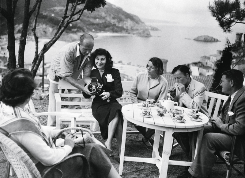 (Original Caption) 11/1956-Costa Brava, Spain: When Frank Sinatra heard of romance brewing between Ava Gardner and Mario Cabre in 1950, he rushed over to Spain with a bagful of jewels to woo Ava back. Here they are sitting in a garden overlooking the beautiful Costa Brava. Sinatra, second from right, chain smokes...
