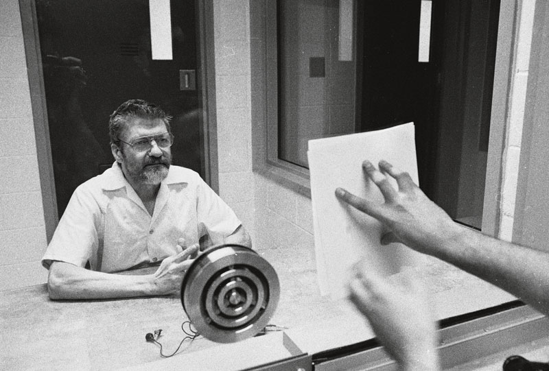 **EXCLUSIVE** American domestic terrorist, luddite, and mathematics teacher Ted Kaczynski looks at a document pressed to the dividing glass by an interviewer during an interview in a visiting room at the Federal ADX Supermax prison in Florence, Colorado, August 30, 1999. (Photo by Stephen J. Dubner/Getty Images)