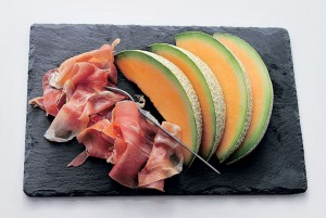 Close-Up Of Meat With Cantaloupe Slices On Cutting Board